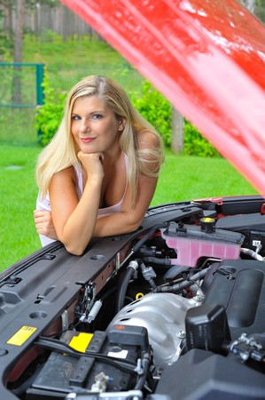Young beautiful woman standing near red car and looking under hood on the engine and other car details photo