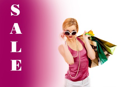 Young pretty shopping woman with lots of bags and sale word  photo