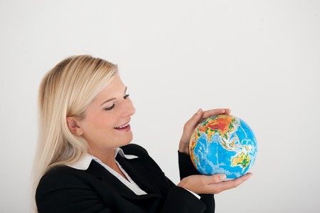 online internet presence: Atractive business woman holding a blue globe in her hand