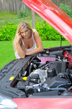 Young beautiful woman standing near red car and looking under hood confused on the engine and other car details photo