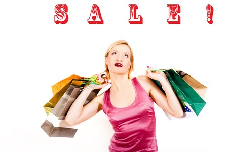 Young pretty shopping woman with lots of bags and sale word above photo