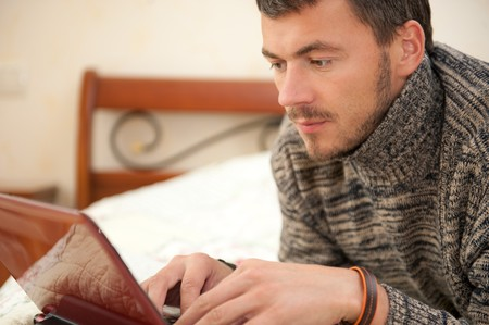 handsome man with laptop computer relaxing on the bed