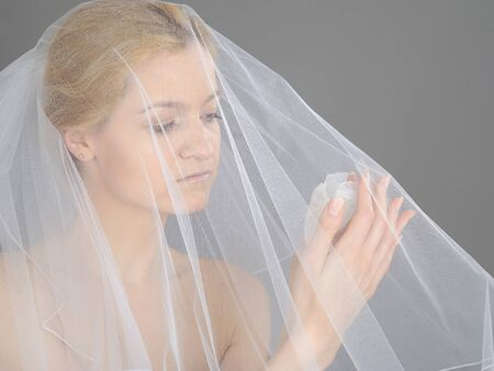 Beautiful young bride in white veil holding heart shaped engagement ring box. gray background photo