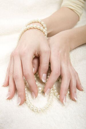 Beautiful hands with perfect french manicure and pearls photo