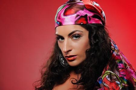 bandana girl: Beautiful gipsy woman with bright make-up. red background Stock Photo