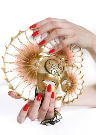 Beautiful hand with perfect red manicure holding carnival mask. youth and beauty concept photo