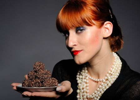 Beautiful retro woman with red lips holding many truffel shocolate sweets. focus on sweets photo