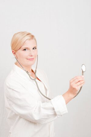 Beautiful female doctor in white medical uniform and stethoscope photo