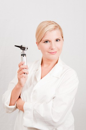 Beautiful female doctor in white medical uniform and tool for checking ear illnesses photo