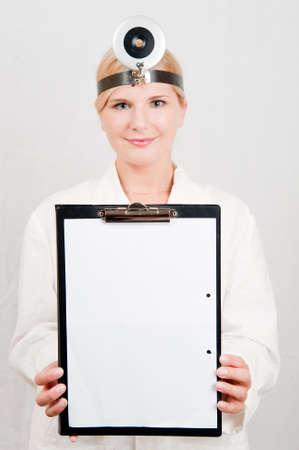 uniforme medico: Hermoso m�dico femenina en blanco uniforme m�dico sosteniendo blanc espacio para el texto