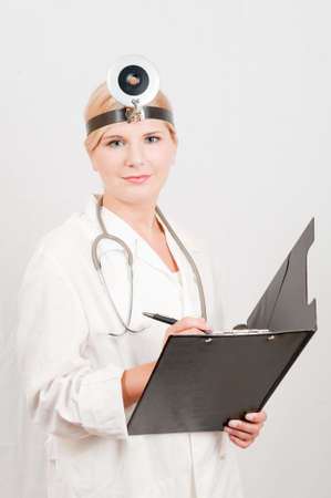 Beautiful female doctor in white medical uniform writing an prescription Stock Photo - 7722281