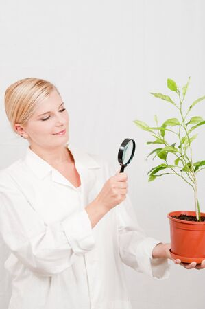Beautiful female botanic scientist in white uniform and green plant photo