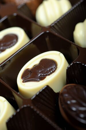 Delicious background of swiss dark chocolates, milk chocolates, pralines and truffles photo
