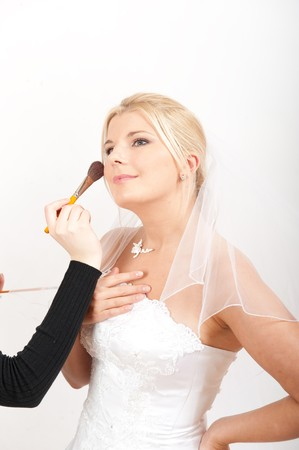 Beautiful bride in white wedding dress making bridal make-up