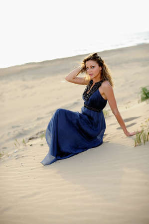 Beautiful fashion woman sitting on the beach in a sand photo