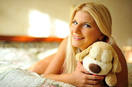 young happy woman relaxing on a bed with a toy photo