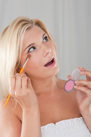 beautiful fresh spa woman with healthy pure skin applying eye shadow with the brush photo
