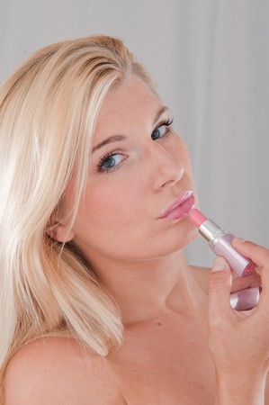 beautiful fresh spa woman with healthy pure skin applying lipstick photo
