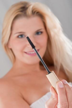 beautiful fresh spa woman with healthy pure skin applying mascara photo