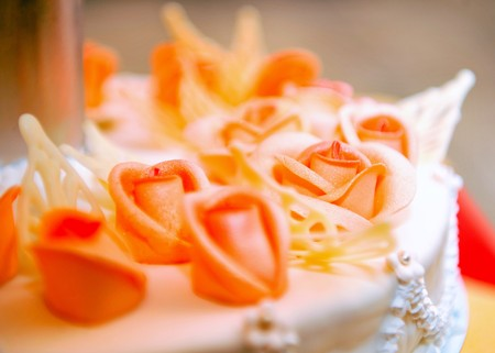 beautiful wedding cake in orange tones with rose flowers photo