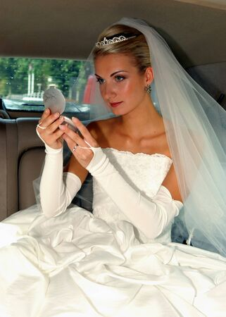 beautiful bride in wedding dress and veil looking in the mirror photo