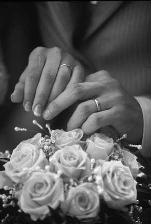 beautiful bride and groom hands with wedding flower bouquet in front