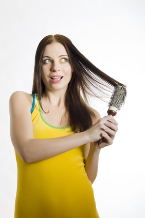 Young beautiful woman in yellow dress with bright funny artistic make-up brushing her long healthy hair. close-up. isolated on white background photo