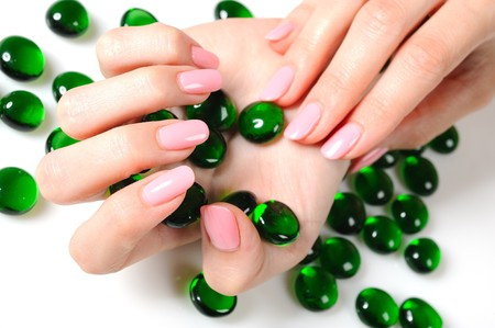 Beautiful hands with perfect nail pink manicure and green decorative stones. isolated on white background Standard-Bild