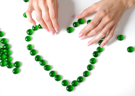 desease: Beautiful hands building a heart sighn from green stones. isolated on white background Stock Photo