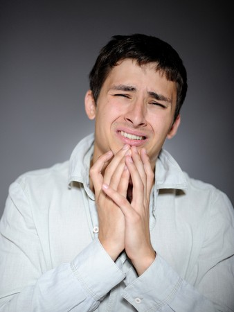 Expressions. Handsome young man feeling fear and crying Stock Photo - 7874157