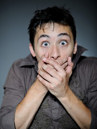 scared man: Expressions. Handsome young man feeling fear and shock  closing mouth with hands Stock Photo