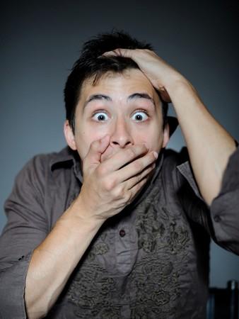 unexpectedness: Expresiones. Apuesto joven sensaci�n de miedo y shock cerrar la boca con las manos  Foto de archivo
