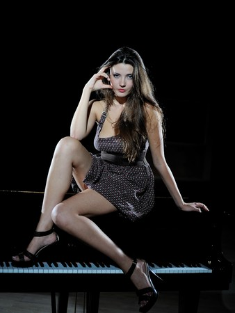 beautiful woman sitting on a black studio piano photo