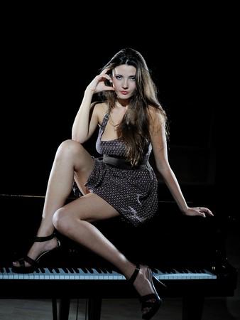 forte: beautiful woman sitting on a black studio piano