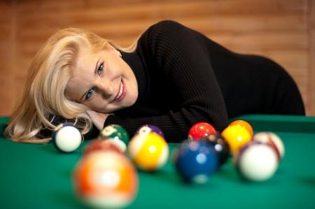 billiard balls on green table and beautiful girl photo