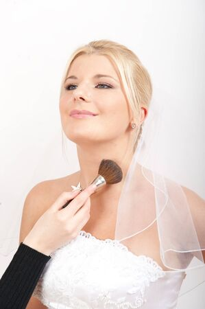 Beautiful elegant bride in white wedding dress applying make-up photo