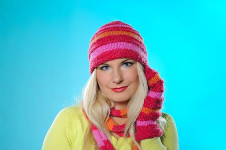 Seasonal portrait of pretty funny woman in hat and gloves smiling. blue background photo