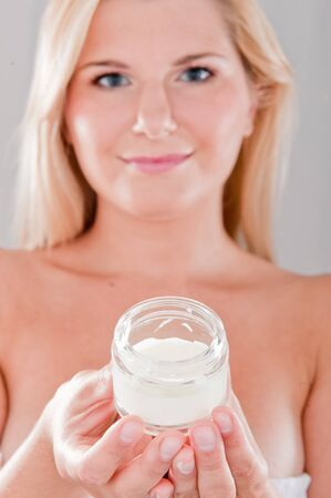 Pretty woman with pure healthy skin holding facial creme Stock Photo - 7874038