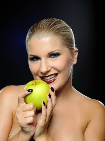 Beautiful woman with bright make-up holding green apple photo