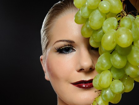 Beautiful woman with bright make-up holding green grapes photo