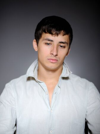 Expressions. Handsome man in white shirt feeling sad and depressed photo