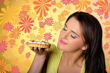 young beautiful girl eating small sweet cake. yellow background Stock Photo - 7874305