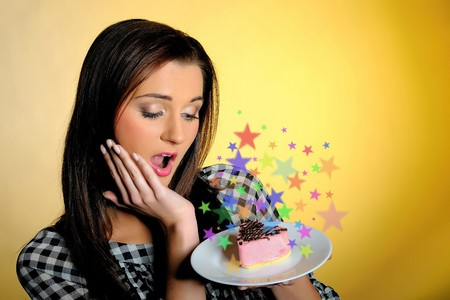 young beautiful girl with small sweet birthsday cake surprised and emotional. yellow background Stock Photo - 7874306