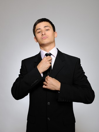Young handsome business man in black suit and tie. gray background photo