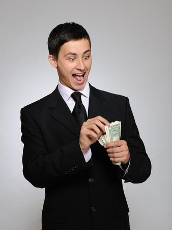 contando dinero: Hombre de negocios apuesto joven en traje negro y corbata contando dinero. fondo gris
