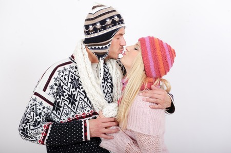 Handsome winter couple in warm clothes huging and kissing photo