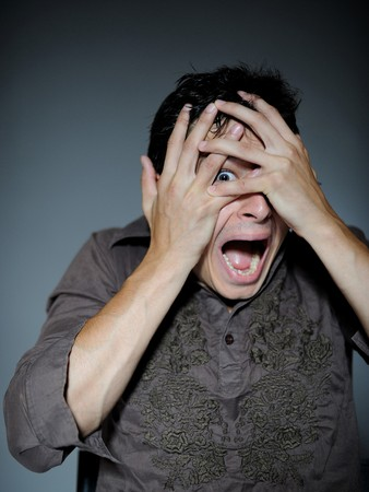 unexpectedness: Expressions. Handsome young man feeling fear with open mouth and closing eyes with hands