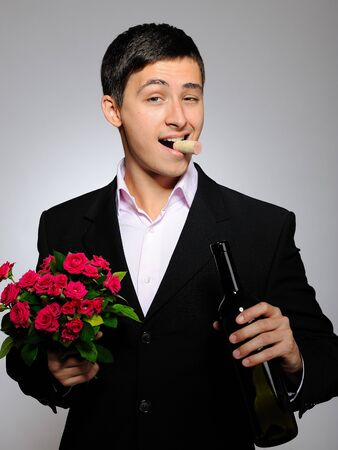 Handsome romantic young man holding rose flower and vine bottle  prepared for a date. gray background photo
