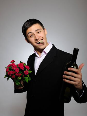 anniversary sexy: Handsome romantic young man holding rose flower and vine bottle  prepared for a date. gray background