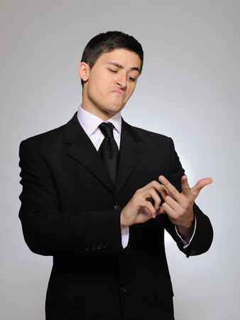 Young handsome business man in a formal suit counting on fingers. studio shot photo